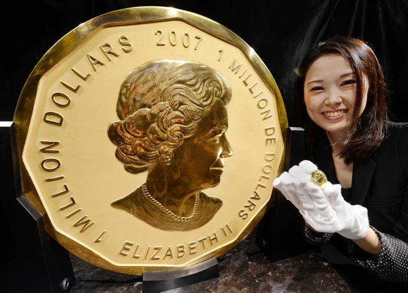 Токио, Япония, 6 ноября. В городе открылась выставка канадской монеты «Золотой кленовый лист» весом 100 кг к 30-летию с начала продаж монет «кленовый лист» (образец монеты в руке ювелира) на территории страны. Фото: TORU YAMANAKA/AFP/Getty Images