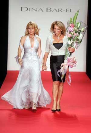 Телевізійний репортер Джанн Карл и модельєр Діна Бар-ел йдут по подіуму на показі колекції Діни Бар-ел - Весна 2006. Фото: Getty Images.