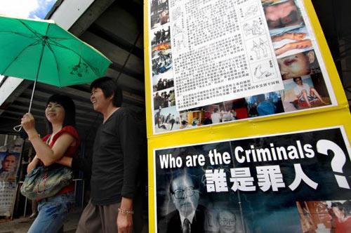 Последователи Фалуньгун проводят акцию протеста с плакатами. Фото: TED ALJIBE/AFP/Getty Images
