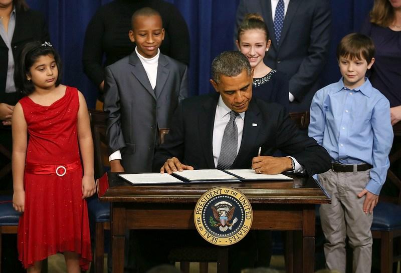 Вашингтон, США, 16січня. Барак Обама підписує виконавчі розпорядження, які роблять жорсткішими правила володіння вогнепальною зброєю. Фото: Mark Wilson/Getty Images