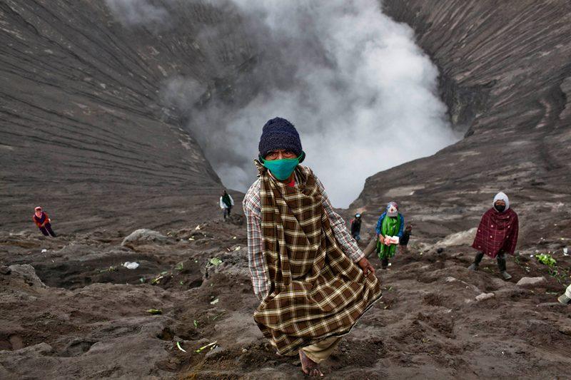 Проболинго, Восточная Ява, Индонезия, 24 июля. Жители собирают пожертвования, которые пилигримы бросают в жерло вулкана Бромо во время фестиваля Ядня Касада, чтобы задобрить вулкан. Фото: Ulet Ifansasti/Getty Images