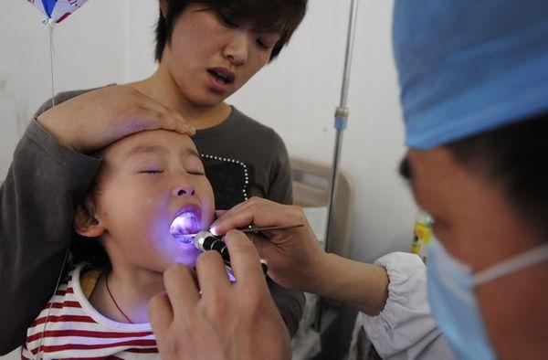 6 травня 2008 р. У м. Куньмін провінції Юньнань лікарі проводять поголовну перевірку всіх дітей на зараження HFMD. Фото з aboluowang.com