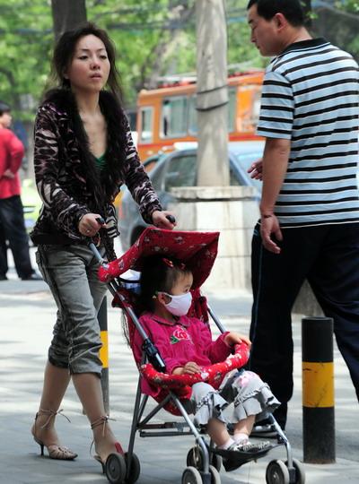 Пекін, 6 травня 2008 р. Батьки надягають на своїх дітей марлеві пов'язки, щоб уберегти їх від зараження HFMD. Фото з aboluowang.com