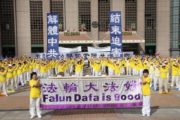 Надпись на плакатах сзади: «Разложить КПК», «Прекратить репрессии». Фото с minghui.org
