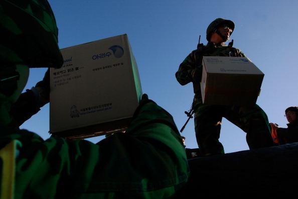 ОСТРІВ YEON PYEONG, ПІВДЕННА КОРЕЯ, 26 листопада: Південнокорейські морські піхотинці у порту вивантажують з човна вантаж. Підсилення військової боєготовності. Фото: Chung Sung-Jun/Getty Images