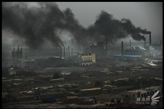 Два «чёрных дракона», выходящие из труб, накрывают весь посёлок в промышленном районе Ласэнмяо Внутренней Монголии. 26 июля 2005 год. Фото: Лу Гуан