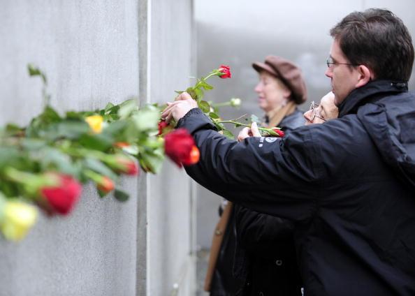 Люди вставляють троянди в щілини стіни під час церемонії на вул. Бернауер-штрассе (Bernauer Strasse). Фото: Getty Images