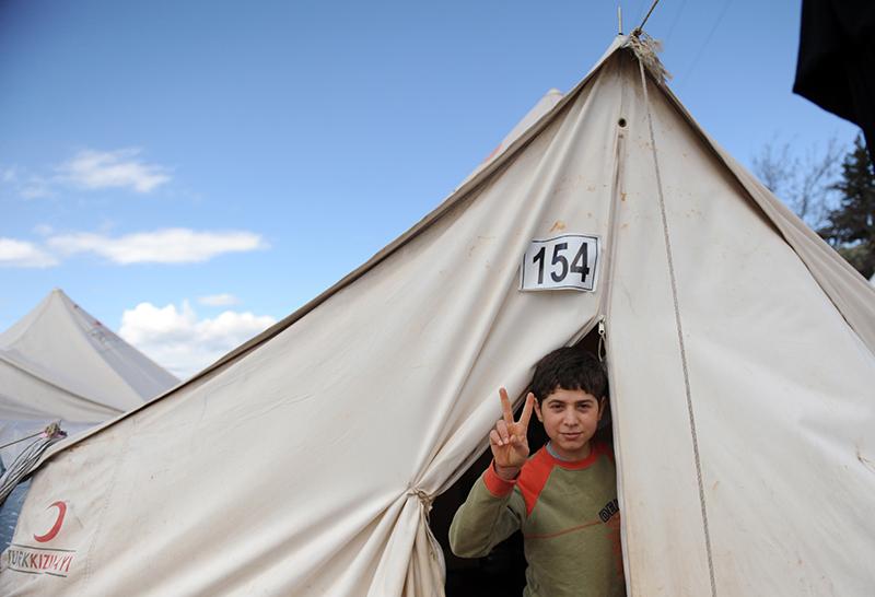 Сирийский мальчик выходит из палатки в лагере беженцев в Турции в районе Рейханлы, 15 марта 2012 года. Фото: BULENT KILIC/AFP/Getty Images
