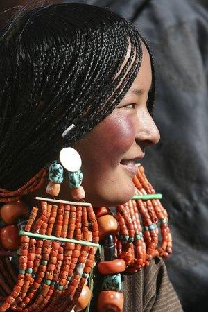 Молода тибетка охоче демонструє свої прикраси для волосся. Належачи до народу, який не має постійного місця проживання, вона гордо носить на собі своє багатство, що складається з коралів і бірюзи. Фото: China Photos/Getty Images