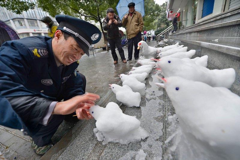 Ханчжоу, Китай, 19 лютого. Снігопади засипали схід країни. Охоронець ліпить птахів зі снігу перед входом у будівлю банку. Фото: ChinaFotoPress/Getty Images