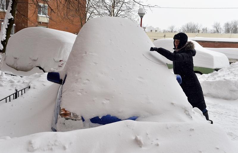 Київ, Україна, 23 березня. Дівчина намагається відкопати машину після сильного снігопаду. Фото: SERGEI SUPINSKY/AFP/Getty Images