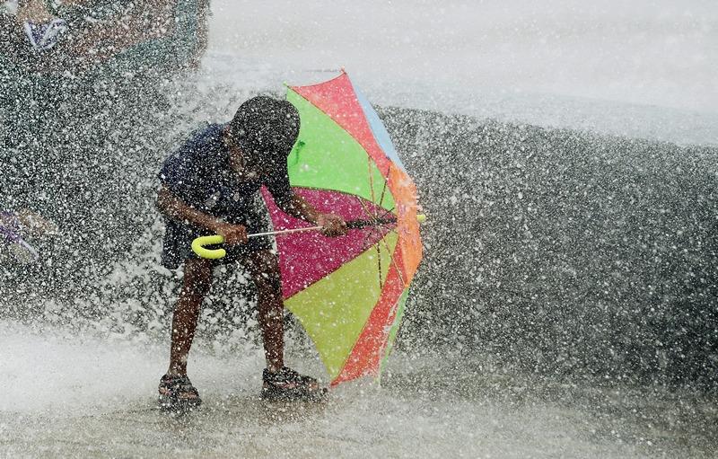 Мумбай, Индия, 25 июля. Мальчик с помощью зонта безуспешно пытается спрятаться от дождя и морских брызг. Фото: PUNIT PARANJPE/AFP/Getty Images