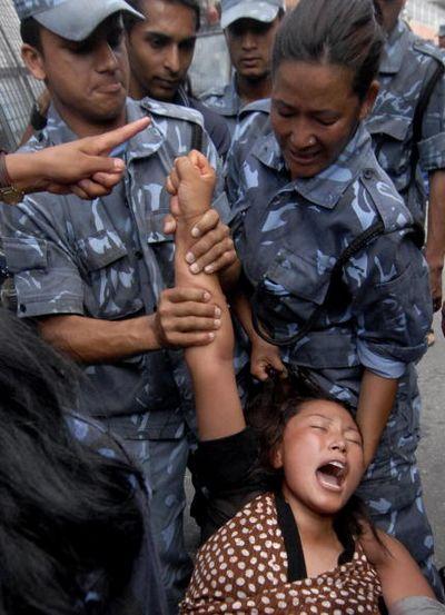 Непальські поліцейські затримують тибетських активістів під час демонстрації біля китайського консульства. Фото: AFP PHOTO/Prakash MATHEMA