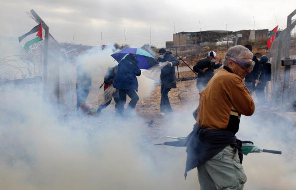 Палестинцы укрываются от слезоточивого газа во время акции протеста против разделительной стены Израиля на Западном берегу вблизи Рамаллы. Власти Израилья говорят, что барьер необходим для безопасности, однако палестинцы рассматривают ее как захват сво