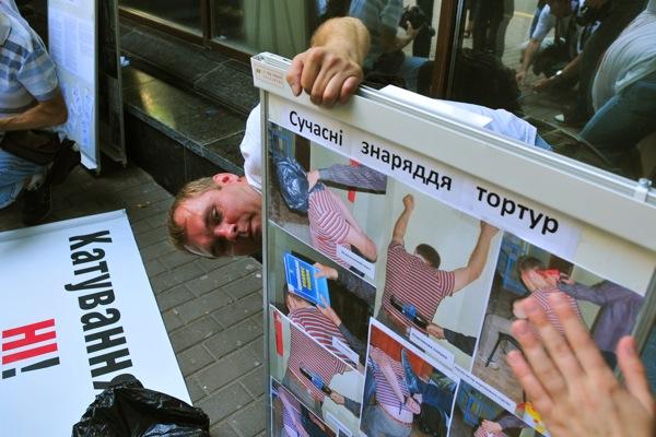Участник акции держит стенд с изображением методов пыток, применяемых в украинской милиции к задержанным. Фото: Владимир Бородин/The Epoch Times