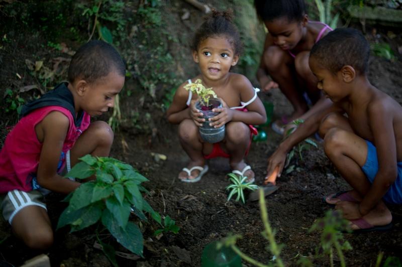 Ріо-де-Жанейро, Бразилія, 7червня. Діти висаджують квіти в місцевому екологічному парку, розбитому на місці колишнього звалища. Фото: CHRISTOPHE SIMON/AFP/Getty Images