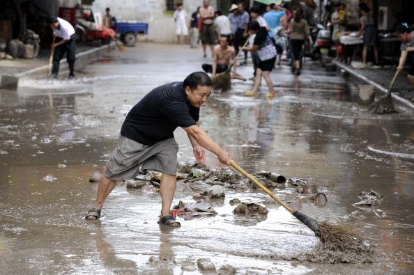 Жители убирают улицу после наводнения. г. Ланси, провинция Чжэцзян. Фото: STR/AFP/Getty Images