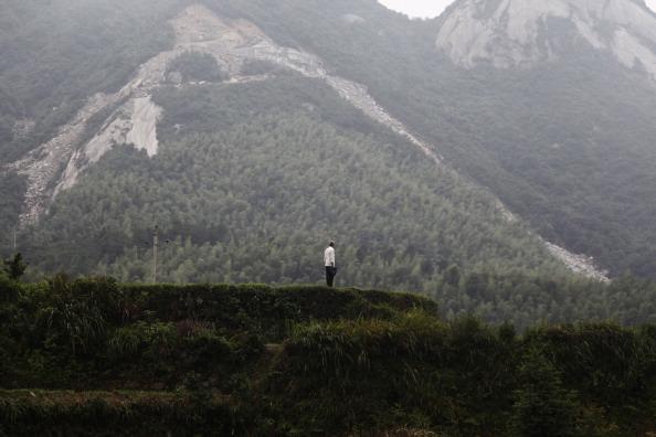 Місцевий житель біля підніжжя гори, по якій спустився зсув. Провінція Хунань, Китай. Фото: STR/AFP/Getty Images