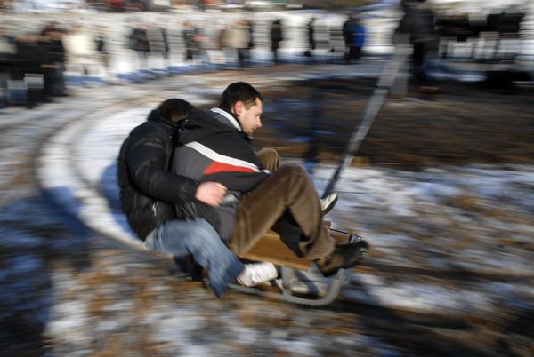 Прокатиться по кругу на санках решались не многие. Добровольцы раскручивали так, что почти все всадники слетали на мокрую землю. Фото: Владимир Бородин/The Epoch Times Украина