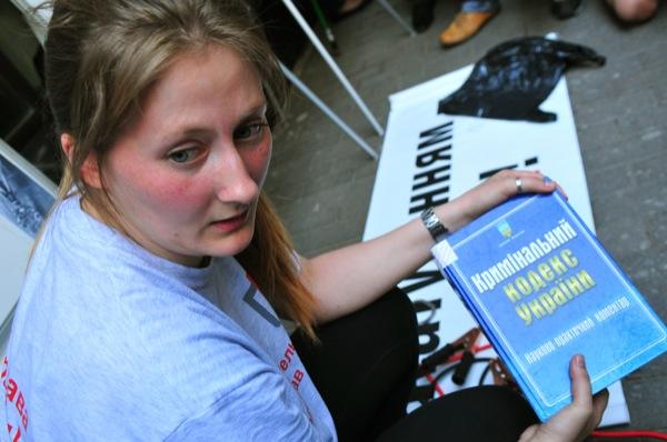 Участница акции, посвященной Международному дню против пыток, держит Криминальный кодек Украины, которыми в милиции избивают задержанных. Фото: Владимир Бородин/The Epoch Times