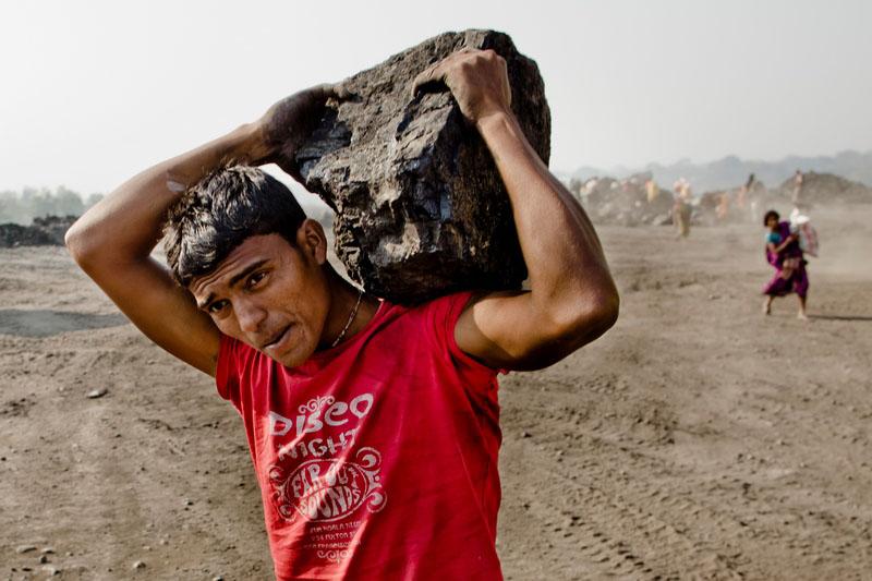 Мужчина несёт глыбу угля. Фото: Daniel Berehulak/Getty Images