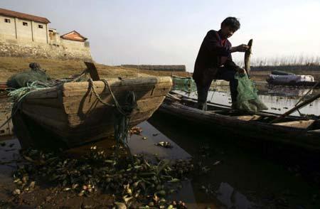 Рыбак показывает, какую рыбу он поймал в озере Дунтин. Фото: China Photos/Getty Images