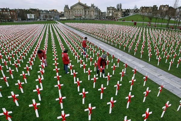 Активісти встановлюють білі хрести з червоними стрічками в Мьюзімплеін (Museumplein) в Амстердамі. Білі хрести є частиною розпочатої кампанії «Зупинимо СНІД» у Всесвітній день боротьби зі СНІДом. Фото: ROBERT VOS / AFP / Getty Images