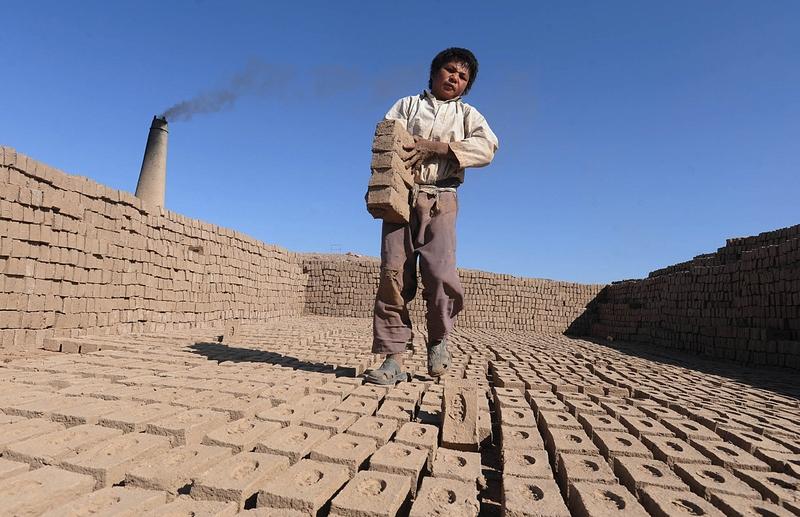 Герат, Афганистан, 29 июля. Рабочий укладывает готовую продукцию на кирпичной фабрике. Фото: Aref Karimi/AFP/GettyImages