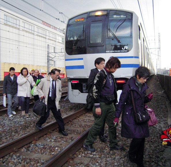 Люди переходят через железнодорожные пути после остановки движения пригородных поездов в городе Funabashi, пригороде Токио после сильного землетрясения в Японии 11 марта 2011. Фото: AFP PHOTO / JIJI PRESS