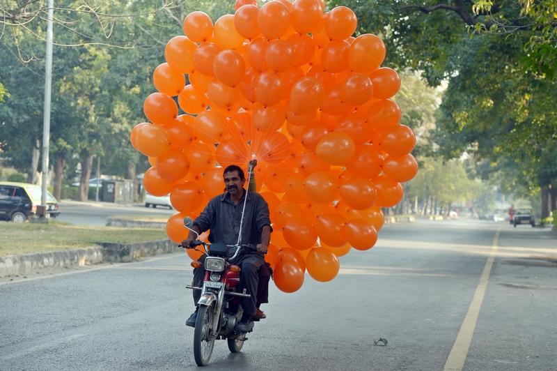 Исламабад, Пакистан, 22 декабря. Торговец везёт на продажу надувные шарики. Фото: FAROOQ NAEEM/AFP/Getty Images