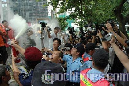 Полицейские Аомына пытаются потушить Факел в защиту прав человека. Фото: Ан Чи/ The Epoch Times