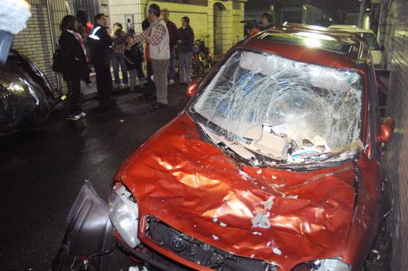 В результате землетрясения силой в 6,4 баллов в Тайбэе, столице Тайваня, водяной бак свалился с верхнего этажа здания на припаркованную машину. Фото: PATRICK LIN/AFP/Getty Images