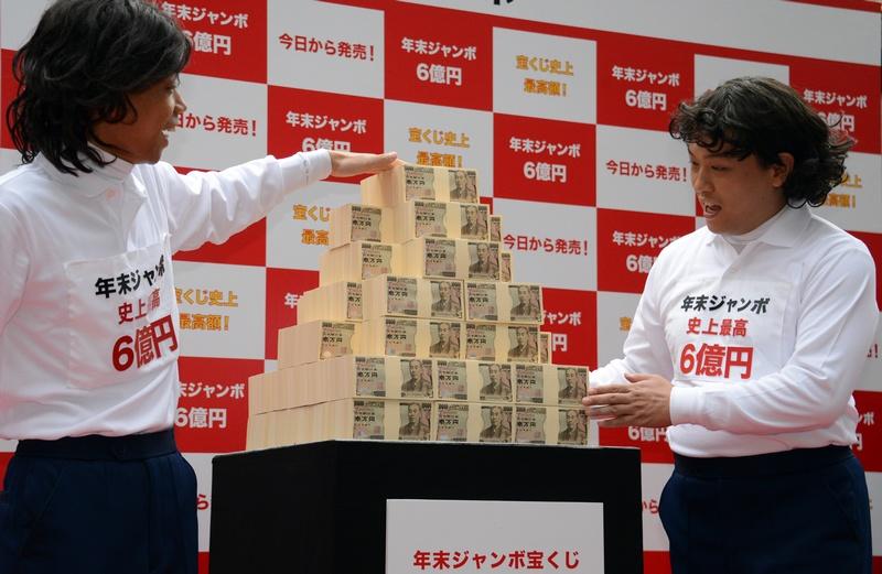 Токио, Япония, 26 ноября. Комедианты Кендзи Тада (слева) и Йоши Ямада демонстрируют 600 млн йен (7,3 млн $), которые будут разыграны в лотерее Jumbo («Суперлотерея») в конце года. Фото: YOSHIKAZU TSUNO/AFP/Getty Images