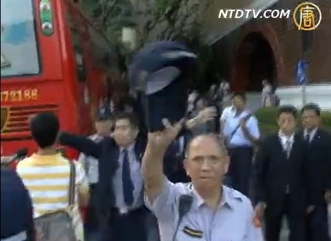 Охорона Хуана Хуахуа забороняє кореспондентам робити відеозйомку. Фото: NTDTV