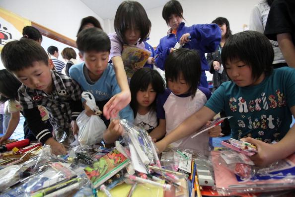 Дети разбирают пожертвованные канцелярские товары на благотворительном мероприятии в г. Отсучи, префектура Иватэ. Фото: Kiyoshi Ota/Getty Images