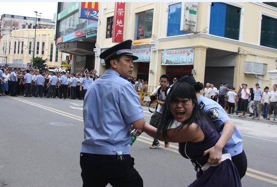 Полицейские арестовывают участницу акции в защиту кантонского диалекта в Гуанчжоу. Фото: The Epoch Times