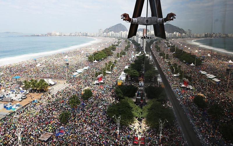 Рио-де-Жанейро, Бразилия, 28 июля. Мужчина фотографирует из окна отеля огромную толпу паломников на пляже Копакабана, ожидающих прибытия папы римского Франциска I. Фото: Mario Tama/Getty Images