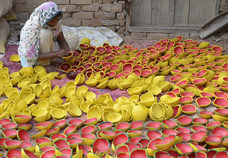 Амритсар, Индия, 4 ноября. Индианка окрашивает светильники для предстоящего фестиваля огней Дивали. Фото: NARINDER NANU/AFP/Getty Images