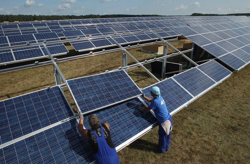Мюнценберг, Німеччина, 4вересня. Робітники монтують панелі сонячних батарей в «Сонячному парку», де планується встановити 85тис. подібних джерел екологічно чистої енергії. Фото: Sean Gallup/Getty Images