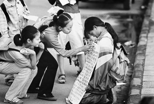 Двое девочек читают надпись на плакате девочки, просящей милостыню на улице. Фото с epochtimes.com