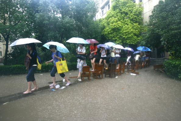Студенты идут на занятия по «мосту» из стульев, камней и досок. г. Ухань, провинция Хубэй. Фото: ChinaFotoPress/Getty Images