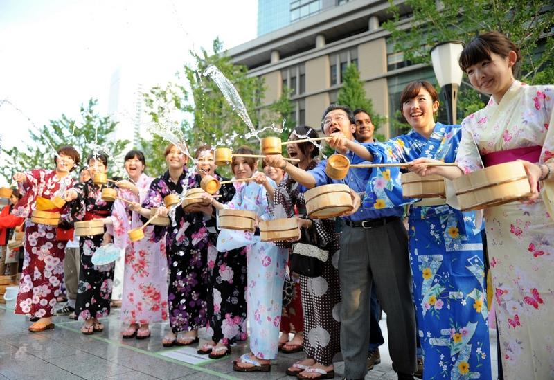 Токио, Япония, 27 июля. Офисные работники в нарядных летних кимоно участвуют в мероприятии разбрызгивания воды для охлаждения тротуаров и уменьшения количества пыли в воздухе. Фото: YOSHIKAZU TSUNO/AFP/GettyImages