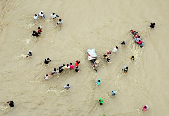 Люди прокладывают себе путь по воде. г. Ланси, провинция Чжэцзян. Фото: STR/AFP/Getty Images