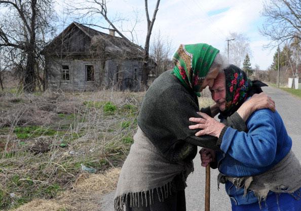 72 летняя Наталья Макеенко (слева) обнимает 82 летнюю Галину Щуку в заброшенной деревне Савичи в Беларуси рядом с 30 километровой зоной отчуждения вокруг Чернобыльской АЭС 21 апреля 2011 года. (VIKTOR DRACHEV/AFP/Getty Images)