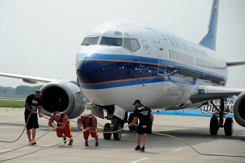 Чжэнчжоу, провинция Хэнань, Китай, 9 июля. 32 силача из 31 страны съехались на Всемирные соревнования самых сильных людей, чтобы потягаться в передвижении лайнера «Боинг 737» весом 34,5 тонны. Фото: AFP/AFP/Getty Images