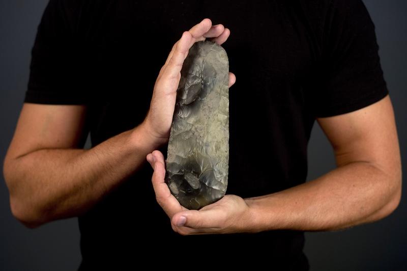 Лондон, Англия, 19 июля. Инженер Денни Мерфи демонстрирует каменный топор, изготовленный во времена неолита (около 6000 лет тому назад), который был найден при сооружении Олимпийского парка. Фото: BEN STANSALL/AFP/GettyImages