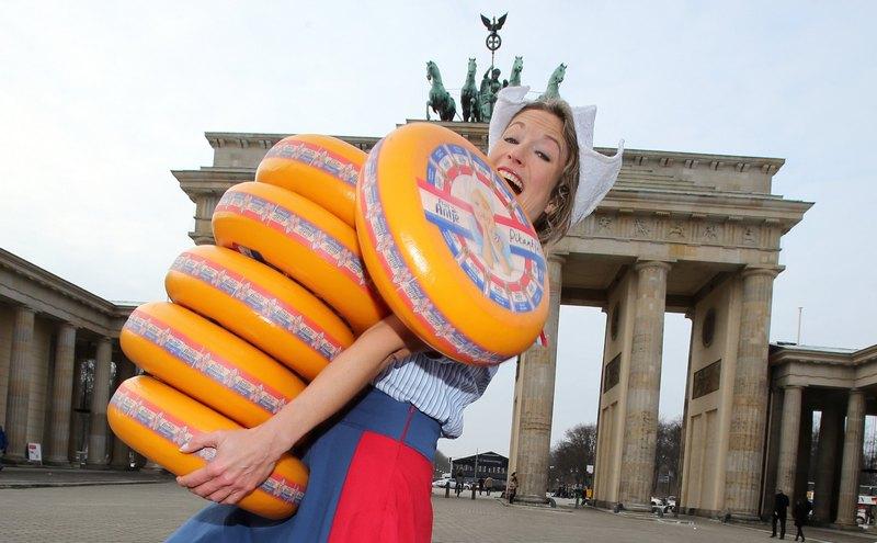 Берлін, Німеччина, 17січня. Дівчина несе сир на виставку-продаж сільськогосподарської продукції «Зелений тиждень». Фото: WOLFGANG KUMM/AFP/Getty Images