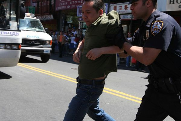 Полицейский арестовал напавшего на последовательницу Фалуньгун китайца. Фото: The Epoch Times