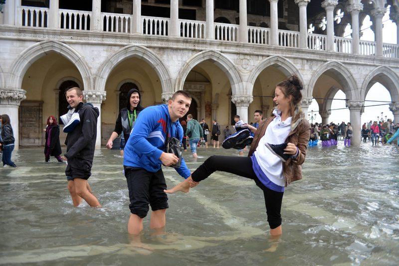 Венеция, Италия, 27 октября. Туристы идут по залитой водой площади святого Марка. Наводнение, или «acqua alta», вызвано африканскими ветрами сирокко, создающими нагонную волну. Фото: ANDREA PATTARO/AFP/Getty Images