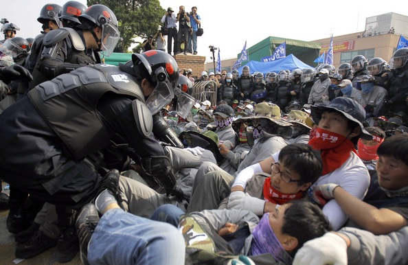 Південнокорейський ОМОН заарештовує страйкарів на найбільшому заводі Yoosung в місті Асан, розташованому більше 80 км на південь від Сеула. Близько 500 робітників затримано рейдом ОМОНу на шостий день страйку, 24 травня 2011 року. Фото: Won Dae-Yeon/Getty